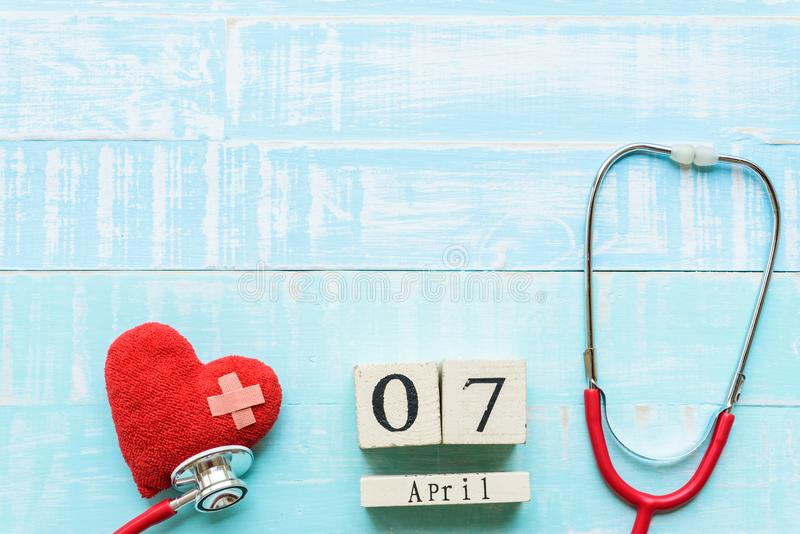 Wooden Block calendar for World health day, April 7. Healthcare and medical concept. Red heart with Stethoscope on Pastel white and blue wooden table royalty free stock photo