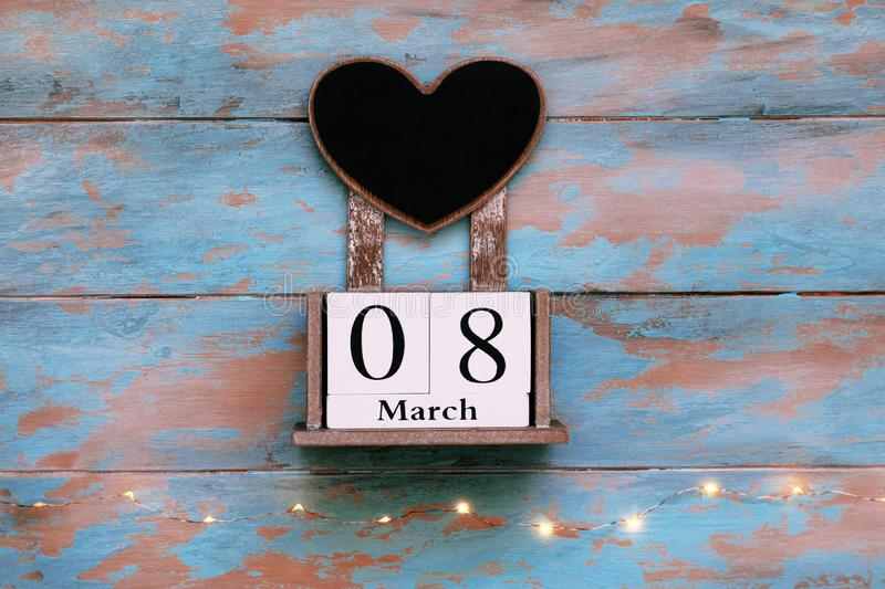Wooden block save the date calendar, March 8, with heart shaped chalk board on vintage blue background with garland royalty free stock image