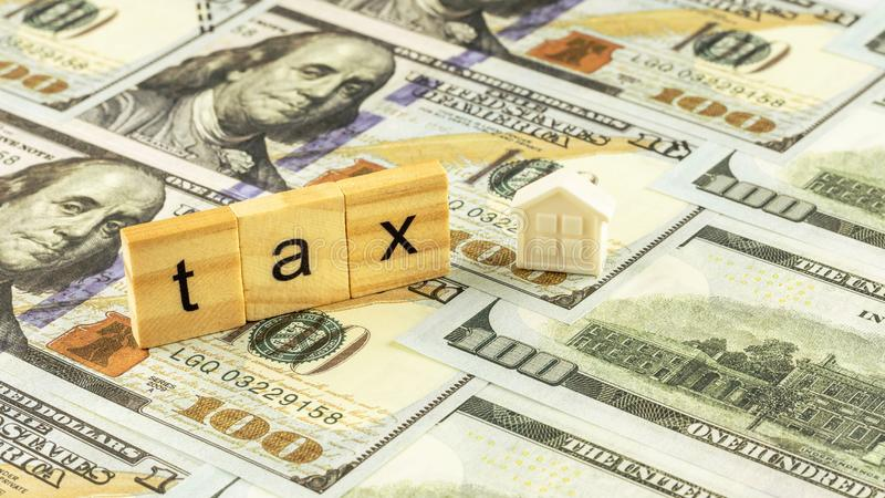 Wooden block and a small home model on dollar bills. Tax Concept. stock image