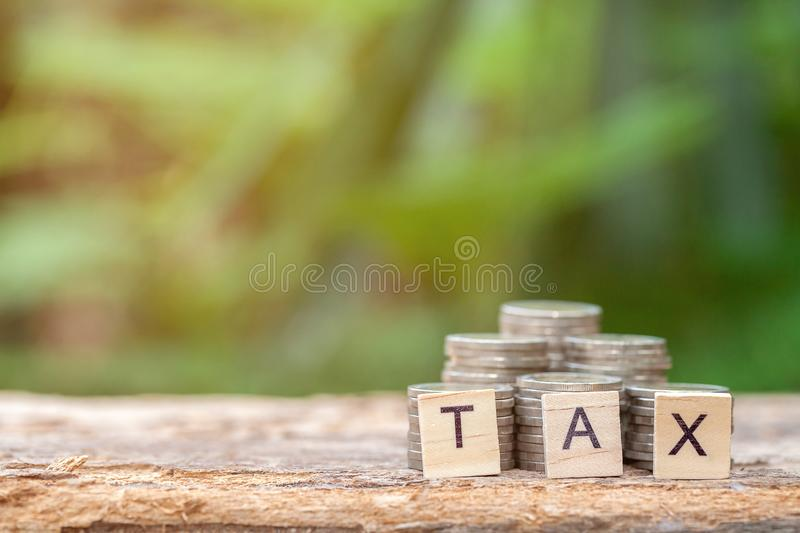 Wooden block with a TAX word and coins stock photos