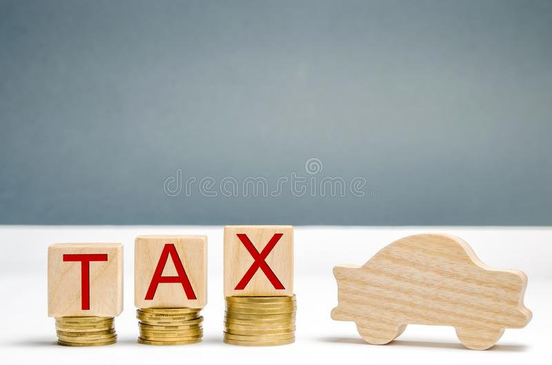 Wooden blocks with coins and the word Tax and wooden auto. The concept of growth taxes on cars. Taxes on the car are increasing. The accumulation of money to royalty free stock image