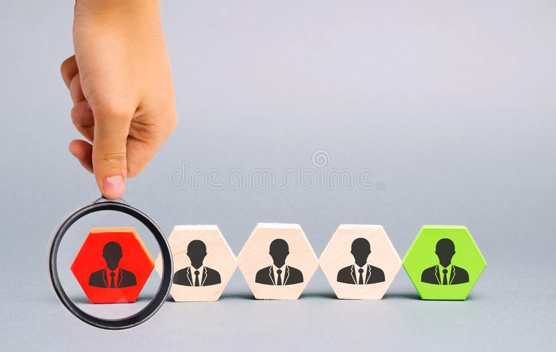 Wooden blocks with the image of workers. The concept of personnel management in the company. Dismissing an employees from a team. Demotion. Bad worker. Staff royalty free stock photos