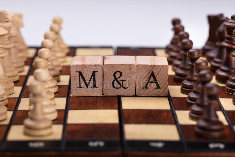 Wooden Blocks With Mergers And Acquisitions Text On Chess Board stock photos