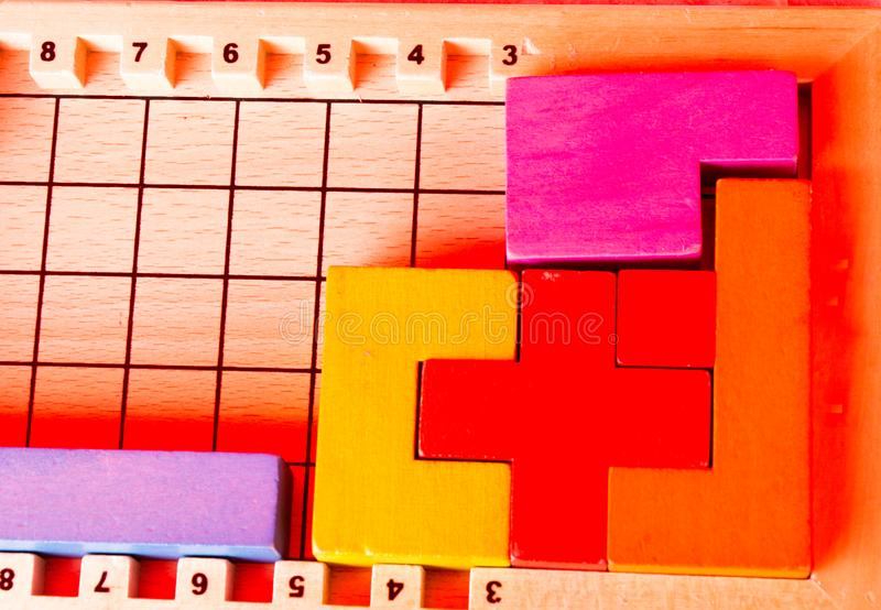Wooden blocks of various colors and shapes. On wooden board royalty free stock images