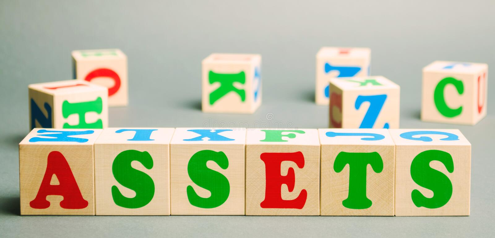 Wooden blocks with the word Assets and randomly scattered cubes. Resource owned by the business. Financial accounting. Money and stock photos