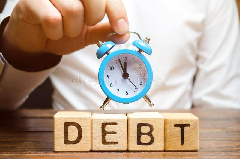 Wooden blocks with the word Debt and the clock in the hands of a businessman. Timely payment of debt. Time to pay off debts. royalty free stock image
