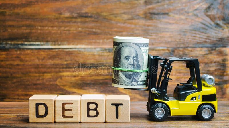 Wooden blocks with the word Debt, dollars and forklift. The amount of money borrowed under certain conditions. Lender and the. Borrower debtor. Concept of stock photos