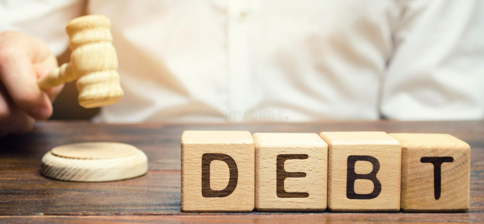 Wooden blocks with the word Debt and judge with a gavel. The concept of judicial punishment for non-payment of debt. Property. Debts. Tax evasion / avoidance stock photo