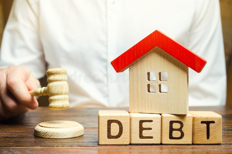 Wooden blocks with the word Debt and a miniature house with a judge`s hammer. Confiscation of property for failure to pay the deb royalty free stock photos