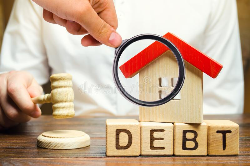 Wooden blocks with the word Debt and a miniature house with a judge`s hammer. Confiscation of property for failure to pay the deb royalty free stock photo
