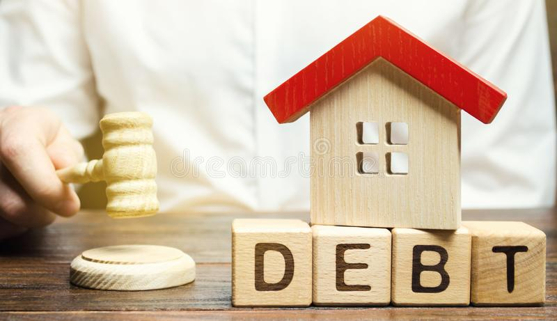 Wooden blocks with the word Debt and a miniature house with a judge`s hammer. Confiscation of property for failure to pay the deb royalty free stock image