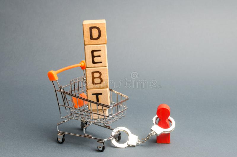 Wooden blocks with the word Debt in a supermarket trolley and a human figurine bound by handcuffs. Mandatory payment of debt. Alimony payment. Pay of a royalty free stock image