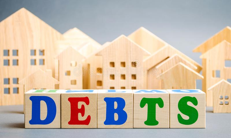 Wooden blocks with the word Debts and miniature houses. Debt concept for housing or mortgage. Real estate and credit, loan.  stock image