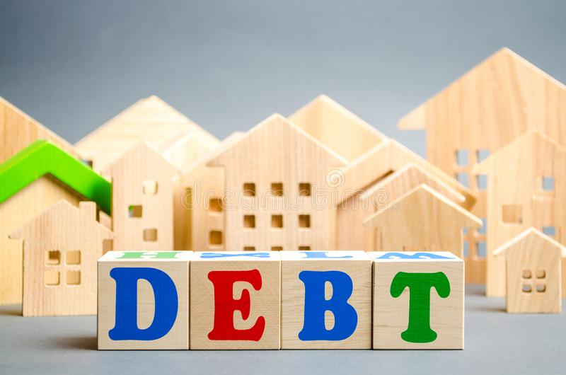 Wooden blocks with the word Debts and miniature houses. Debt concept for housing or mortgage. Real estate and credit, loan.  stock photo