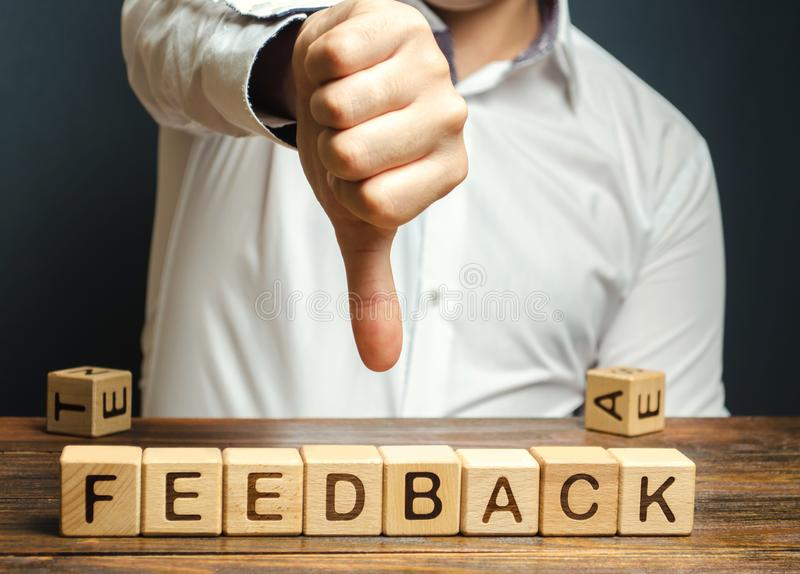 Wooden blocks with the word Feedback and finger down. The concept of the bad rating of hotels and restaurants. The evaluation of. Visitors. Quality level, low stock photo