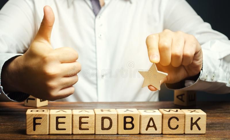 Wooden blocks with the word Feedback and hand up. The concept of the rating of hotels and restaurants. The evaluation of visitors. Quality level, good service royalty free stock photography