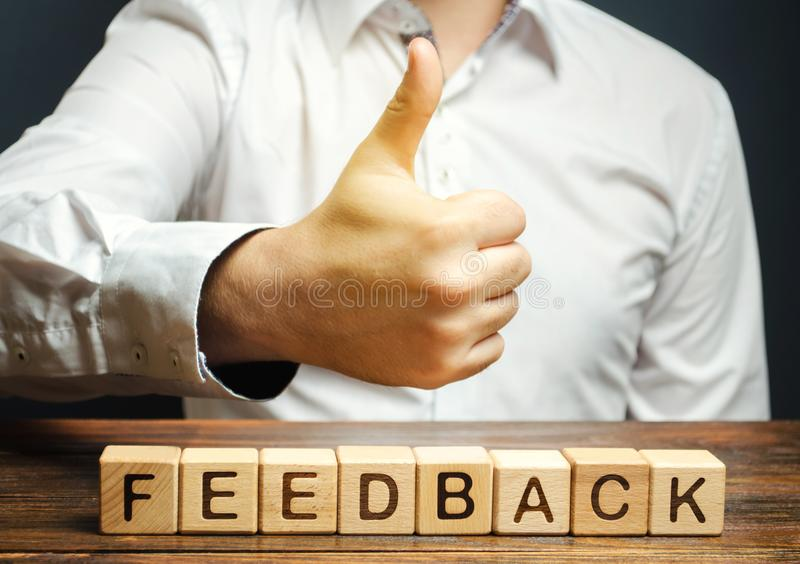 Wooden blocks with the word Feedback and hand up. The concept of the rating of hotels and restaurants. The evaluation of visitors. Quality level, good service royalty free stock image