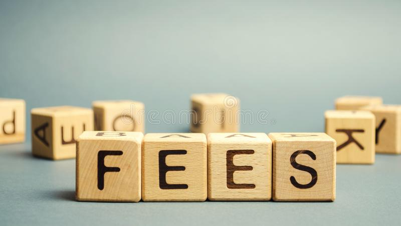 Wooden blocks with the word Fees and randomly scattered cubes. Fixed price charged for a specific service. Business and finance. Concept. Costs, charges stock photo