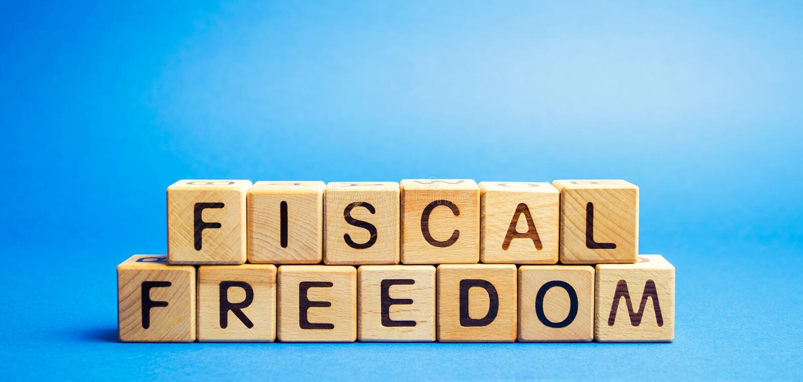 Wooden blocks with the word Fiscal freedom. Tax burden imposed by government. Taxation. Taxes concept. Business and Finance.  royalty free stock photo