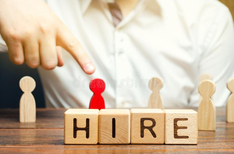 Wooden blocks with the word Hire. Headhunter selects a person from the crowd. Good choice. Human Resource Management. Recruiting royalty free stock photography