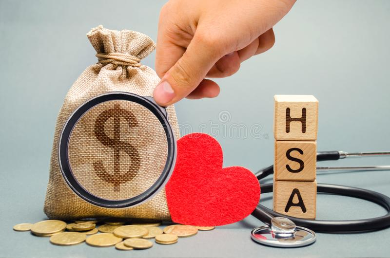Wooden blocks with the word HSA and money bag with stethoscope. Health savings account. Health care. Health insurance. Investments stock photo
