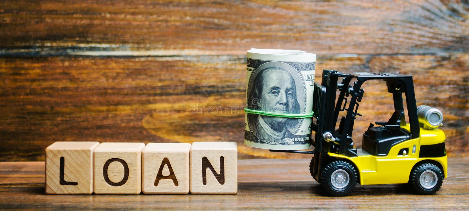 Wooden blocks with the word Loan and forklift. Credit provided by the lender to the borrower at a certain interest for the use of. Money. Bank credits. Commerce royalty free stock photography