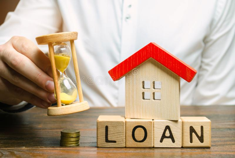 Wooden blocks with the word Loan, miniature house and hourglass in the hands of a businessman. The concept of buying an apartment stock image