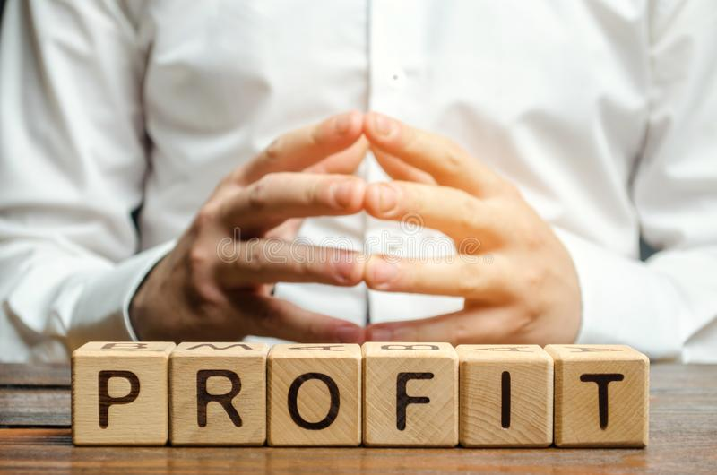 Wooden blocks with the word Profit and businessman. Analysis of profits in the company. Strategy to improve business performance. Profit is below expected. Low royalty free stock images