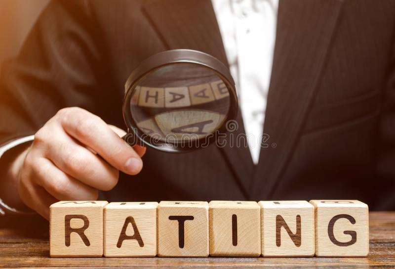 Wooden blocks with the word Rating and a magnifying glass in the hands of a businessman. The concept of studying the rating of the royalty free stock images