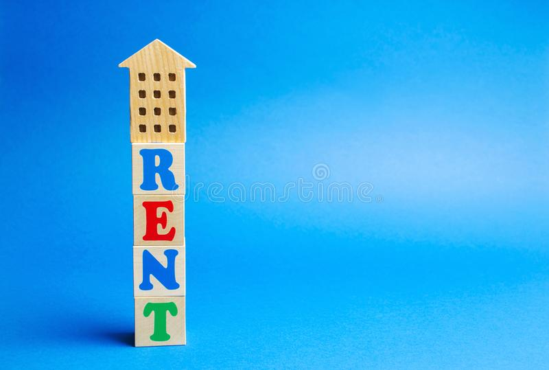 Wooden blocks with the word rent and wooden house. The concept of rental housing. Rent an apartment or home. Payment for renting. Real Estate Agent Services stock images