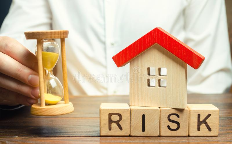 Wooden blocks with the word Risk, the house and the clock. The concept of non-payment of interest rates on mortgages. Real estate. Investment risk. Loss of royalty free stock photo