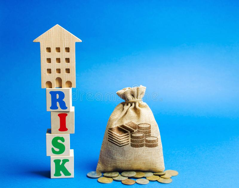 Wooden blocks with the word Risk and a miniature house with a money bag. Real estate investment risk. Risky investments. Loss of. Property for non-payment royalty free stock photos