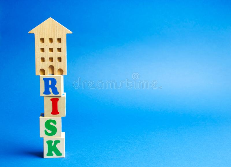 Wooden blocks with the word Risk and a miniature house. Real estate investment risk. Risky investments. Loss of property for non-. Payment. Debts. Mortgage tax royalty free stock image