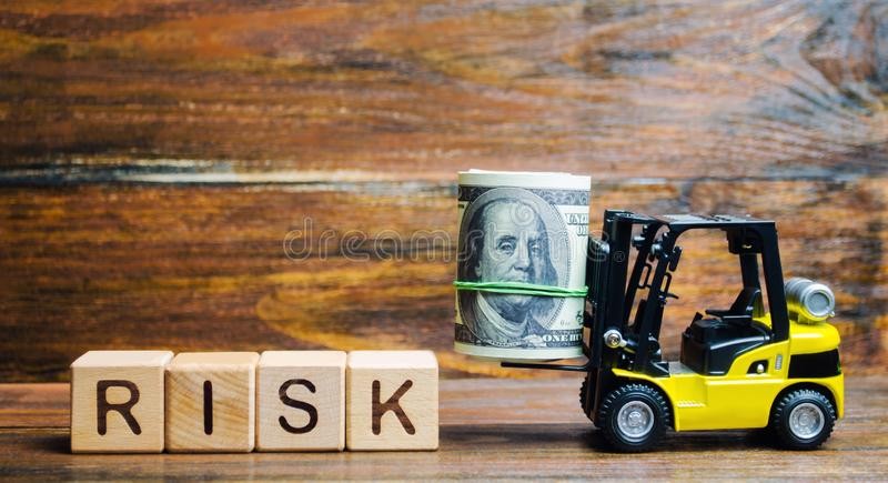 Wooden blocks with the word Risk, money and a forklift. Financial and commercial risk concept. Investing in a business. Risks stock photography