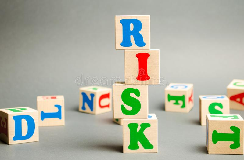 Wooden blocks with the word Risk and randomly scattered cubes. Management, cost assessment, business and investment safety. Strengthen business resilience and stock photo