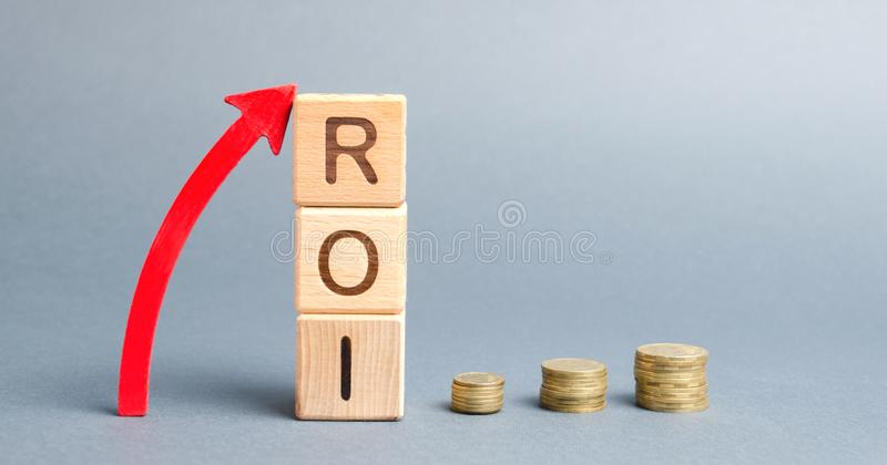 Wooden blocks with the word ROI and arrow up. High level of business profitability. Return on investment, invested capital, rate. Success. Growth stock photography