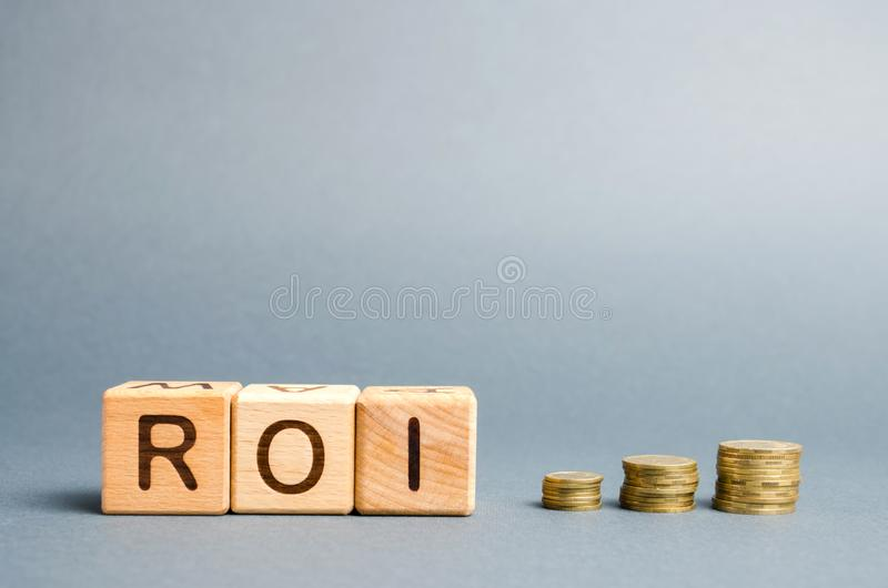 Wooden blocks with the word ROI and coins. High level of business profitability. Return on investment, invested capital, rate. Success. Growth. Profitability royalty free stock images