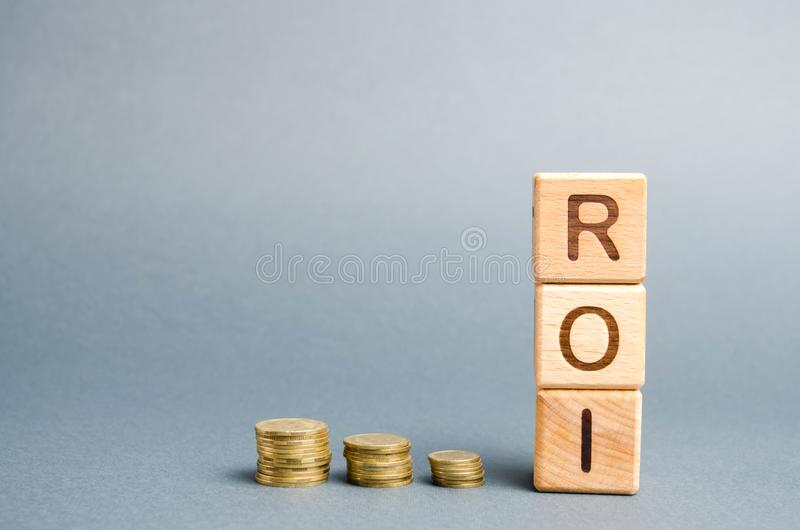 Wooden blocks with the word ROI and coins. High level of business profitability. Return on investment, invested capital, rate. Success. Growth. Profitability royalty free stock image