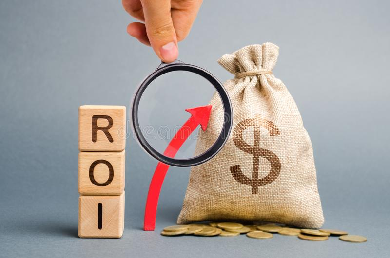 Wooden blocks with the word ROI and the up arrow with the money bag. High level of business profitability. Return on investment,. Invested capital, rate royalty free stock images