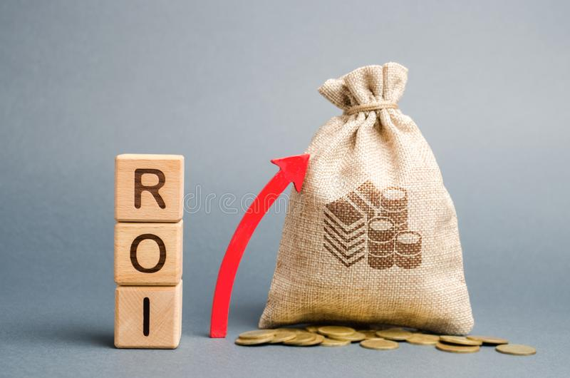 Wooden blocks with the word ROI and the up arrow with the money bag. High level of business profitability. Return on investment,. Invested capital, rate royalty free stock image