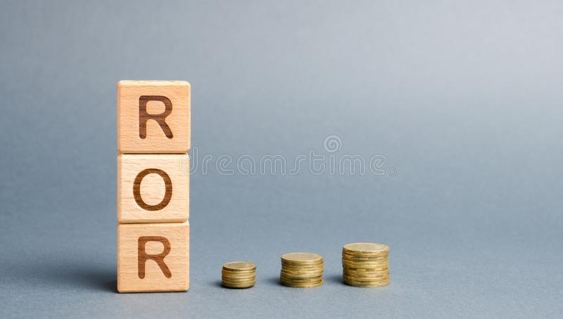 Wooden blocks with the word ROR and coins. High level of business profitability. Return on investment, invested capital, rate. Success. Growth. Profitability stock image