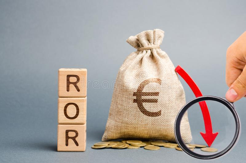 Wooden blocks with the word ROR, money bag and down arrow. Financial ratio illustrating the level of business loss. Return on. Investment. Recession. Lower stock photos