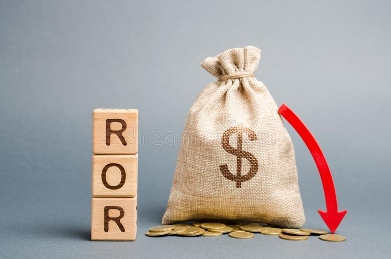Wooden blocks with the word ROR, money bag and down arrow. Financial ratio illustrating the level of business loss. Return on. Investment. Recession. Lower royalty free stock image