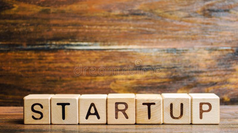 Wooden blocks with the word Startup. Temporary structure designed to find and implement a scalable business model. The concept of. Raising funds for a startup stock photography