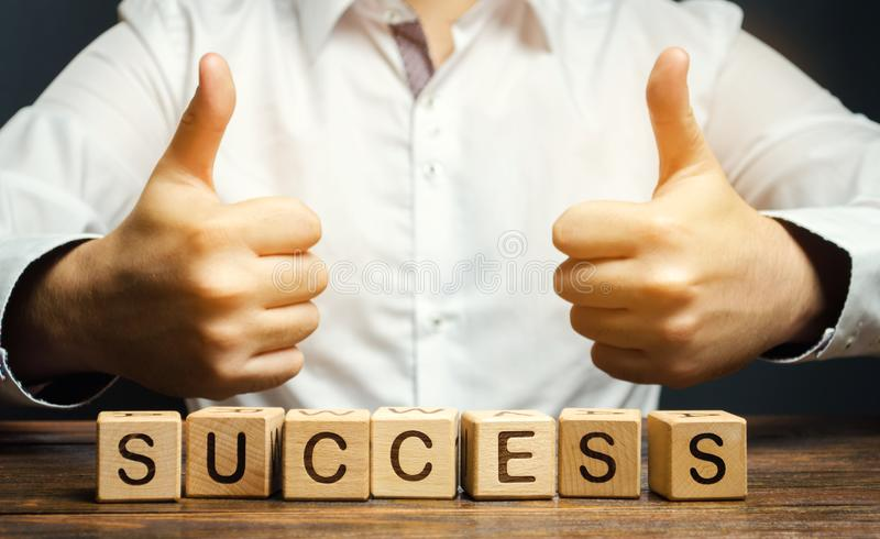 Wooden blocks with the word Success and businessman. Successful business concept. Achieving the goal, overcoming difficulties. The stock images