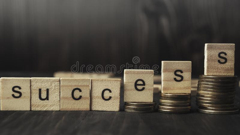 Wooden blocks with the word Success. And coins on wooden background royalty free stock photography