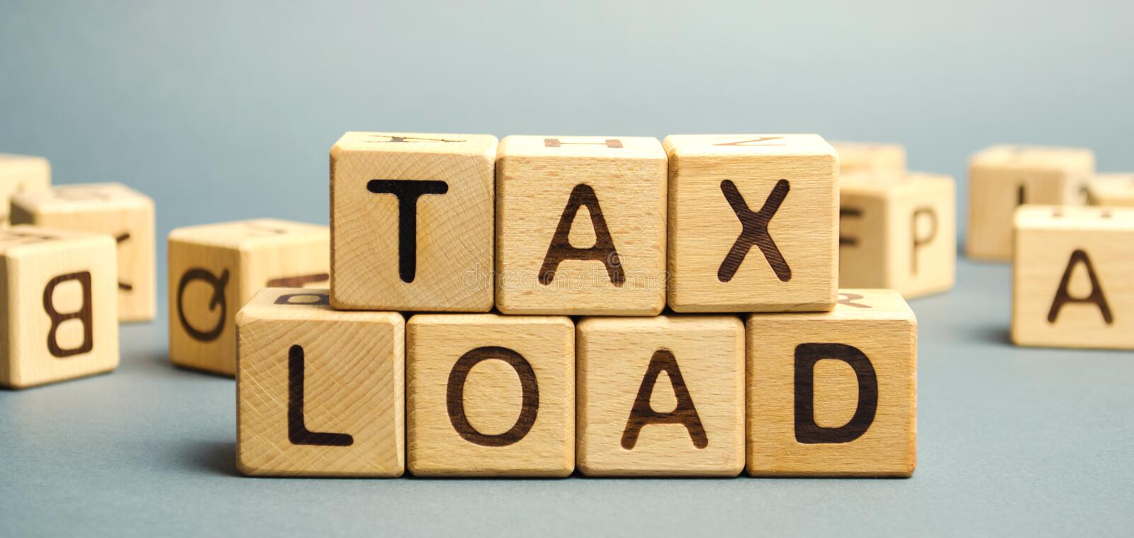 Wooden blocks with the word Tax load and randomly scattered cubes. Measure of the tax burden imposed by government. Taxation. Taxes. Business and finance royalty free stock image