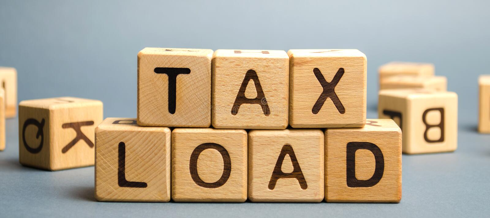 Wooden blocks with the word Tax load and randomly scattered cubes. Measure of the tax burden imposed by government. Taxation. Taxes. Business and finance stock photos