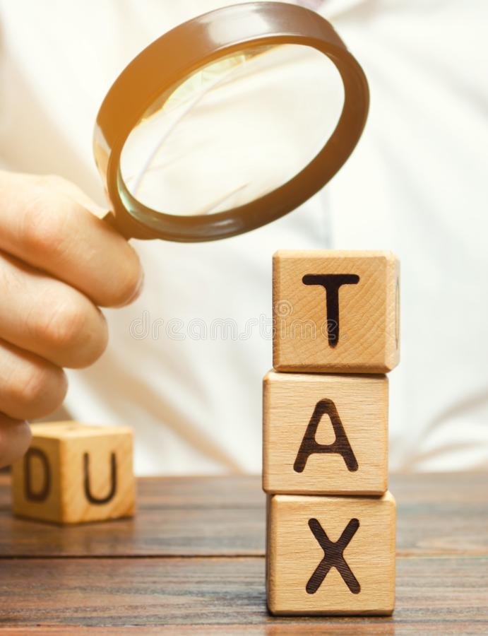 Wooden blocks with the word Tax and a magnifying glass in the hands of a businessman. The concept of studying the size of taxes. royalty free stock photos