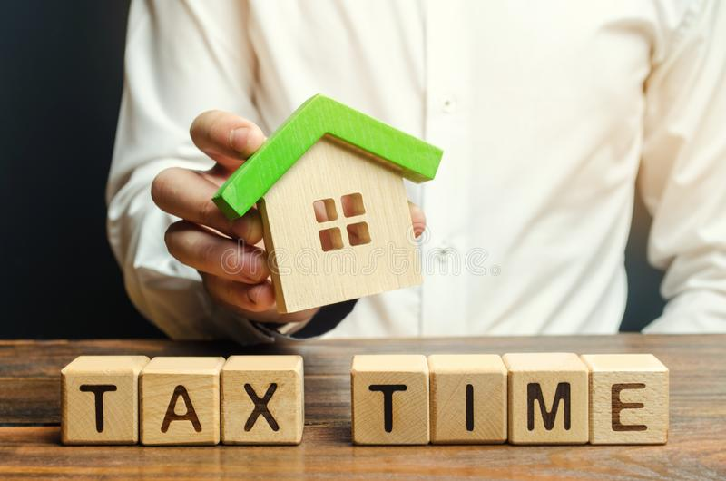 Wooden blocks with the word Tax time and a miniature house in the hands of a businessman. The concept of paying tax for housing. And property. Debt payment royalty free stock image